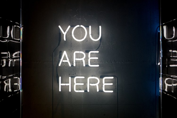 Neon sign that reads 'you are here'
